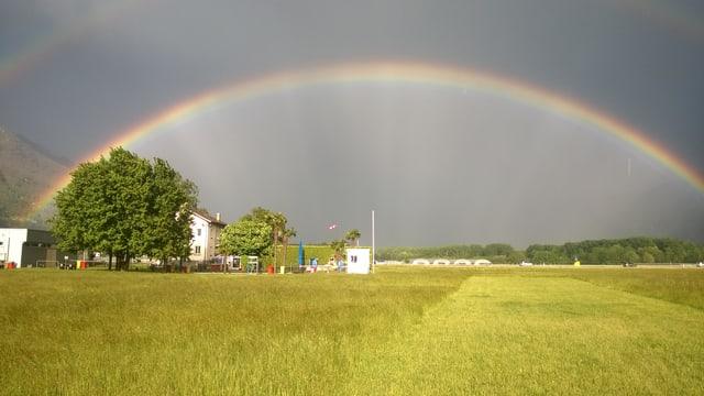 Grüne Wiese und Gebäude des Flugplatzes mit Windsack. Grosser Regenbogen über das ganze Bild. Im Hintergrund dunkle Wolkenwand.