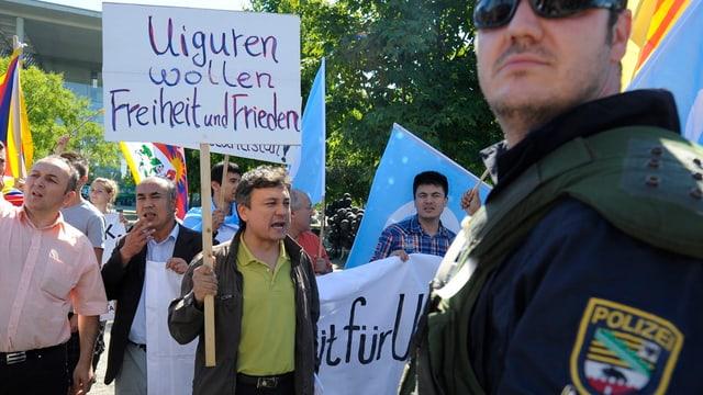 Uiguren in Deutschland halten ein Transpartent hoch.