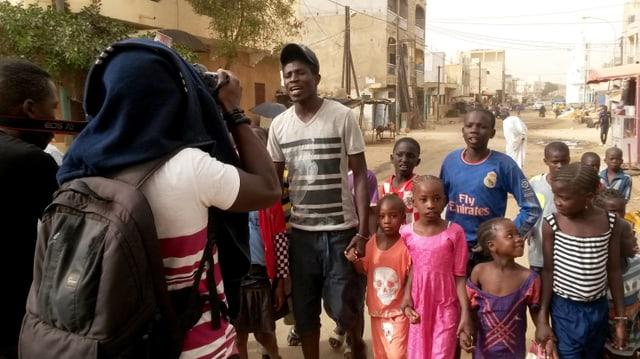 Ein Mann rappt, begleitet von einer Gruppe Kinder, und wird dabei von einem anderen gefilmt.