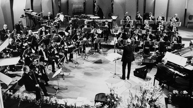 Schwarz-Weiss Fotografie mit dem grossen Orchester in einem grossen Konzertsaal.