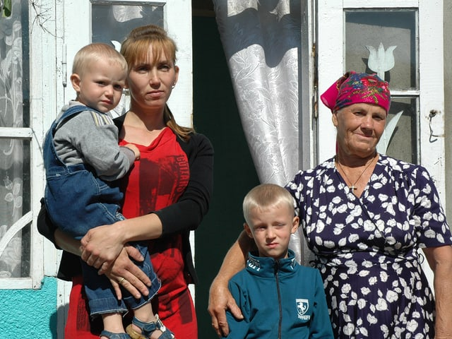 Die Mutter, diie Grossmutter und die zwei Söhne posieren vor dem Haus fürs Foto.