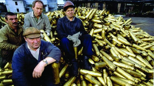 Handwerker in Arbeitskleidung sitzen auf einem grossen Haufen alter Munitionskartuschen aus Messing.