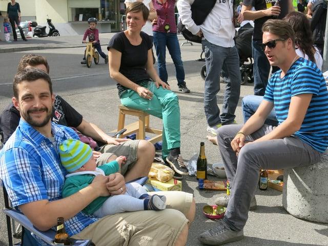Vater, Kind, Mutter, Kollegen sitzen um Getränke und lachen.