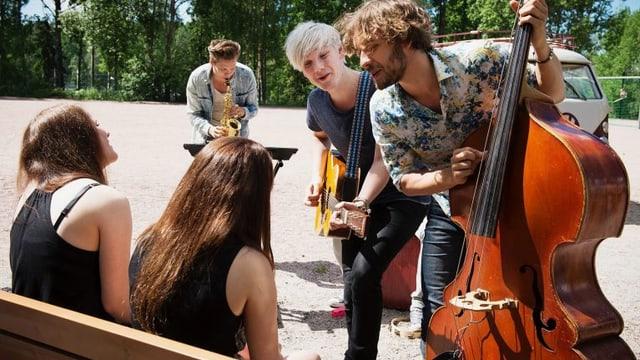 Zwei Frauen sitzen auf einer Parkbank und werden von drei Musikern mit Gitarre, Kontrabass und Saxophon mit einem Ständchen überrascht.