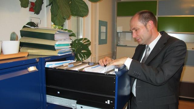 Ein Mann steht vor einem Büromöbel und durchsucht in der geöffneten Schublade die Hängeregistratur.