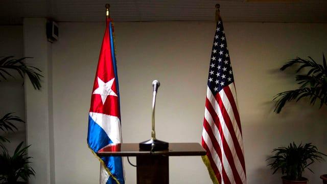 Rednerpult vor Flaggen der USA und Kuba.