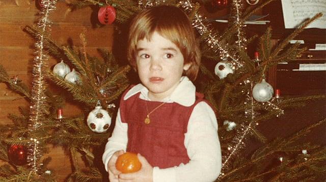Joelle Beeler im Alter von dreieinhalb Jahren vor dem Weihnachtsbaum. Die Fussballkugeln im Baum hat sie erst jetzt entdeckt.