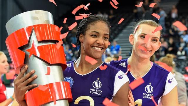 Zwei Volero-Spielerinnen mit einem Pokal.