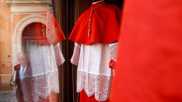 An Mann läuft an einem Schaufenster vorbei, in dem Bischofsgewänder angeboten werden.