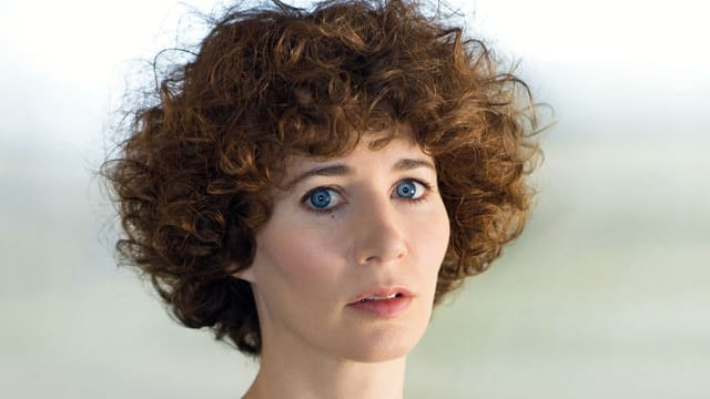Miranda July hat lockiges braunes Haar und blaue Augen.