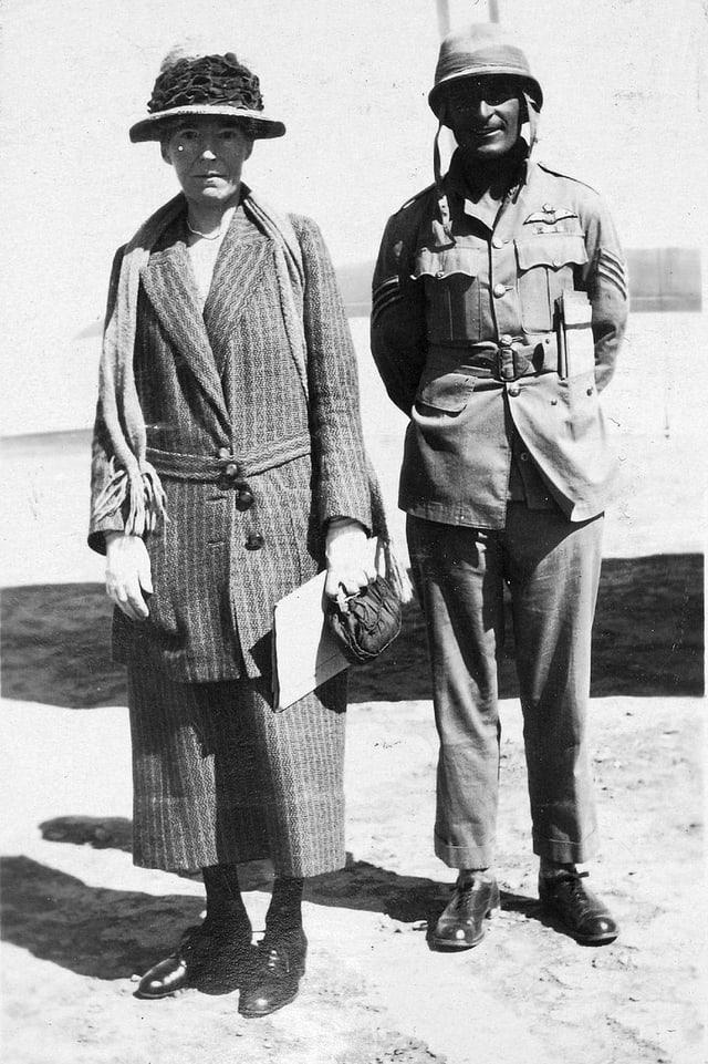 Eine Frau mit Hut steht neben einem Soldaten.