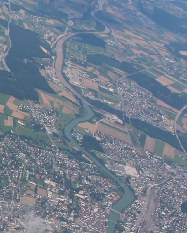Ein Flugbild des Mittellandes mit Feldern, Wäldern und Siedlungsgebiet. Gut ist die Aare wie eine Schlange sichtbar. Erst ist die blau, mit dem Einfliessen der Emme wird sie drecki-braun.