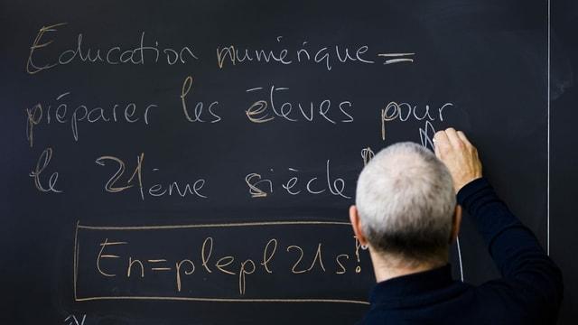 Mann schreibt etwas auf Französisch an eine Wandtafel
