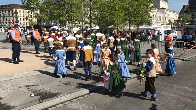 Kleine Kinder in blauen und grünen Röcken
