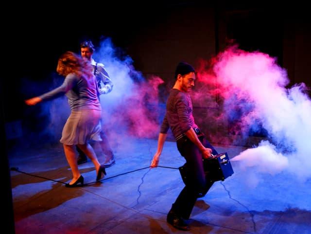 Eine Frau und zwei Männer auf der Bühne, Rauch und lila Licht, einer der Männer reitet auf einem Transistor.
