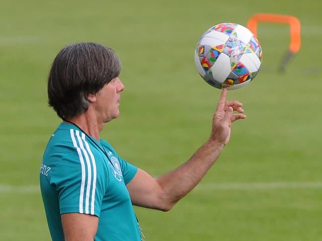 Bundestrainer Jogi Löw jongliert mit dem Ball.