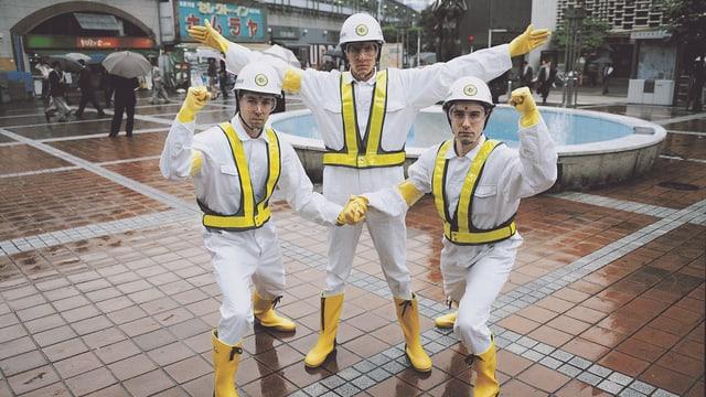 Drei Männer posieren mit ausgestreckten Armen, die tragen wiesse Schutzanzüge und Helme.