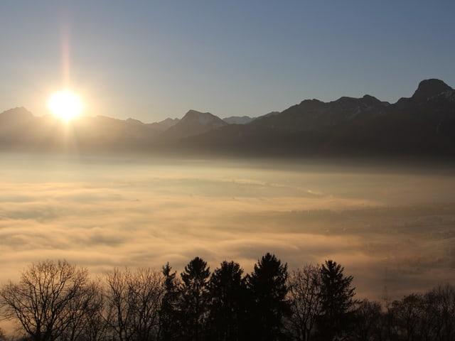 Die Sonne geht auf, hinter einer Bergkette. Im Vordergrund liegt das Nebelmeer.