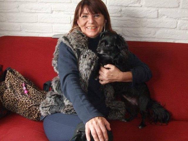 Frau mit Hund auf rotem Sofa