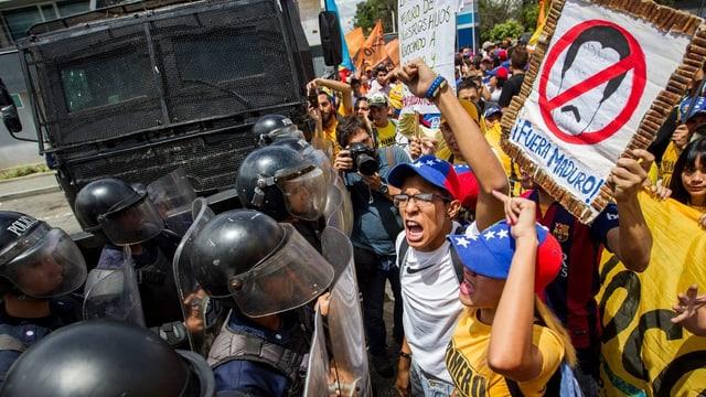 Links Polizisten mit Helmen, rechts Demonstranten, ein Schild «Maduro, raus!»