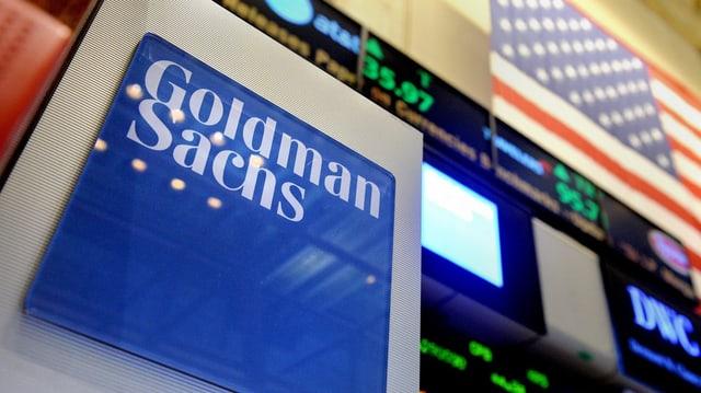 Ein blau-weisses Goldman-Sachs-Schild an der New Yorker Börse, im Hintergrund eine US-Flagge.