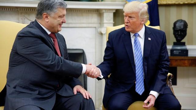 Zwei Männer schütteln sich im Oval Office die Hände.