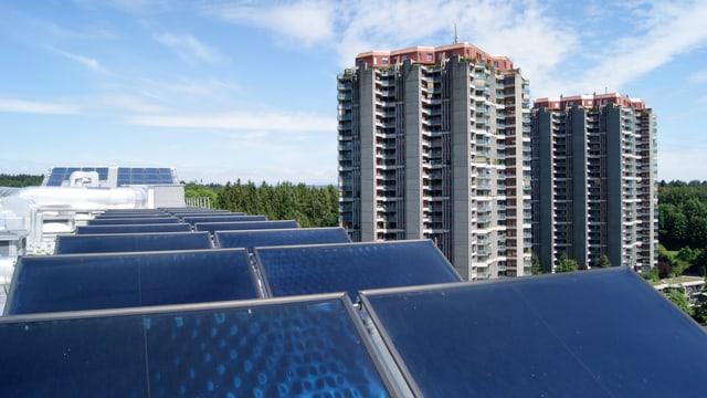 Solarzellen auf einem Dach. Im Hintergrund Hochhäuser.