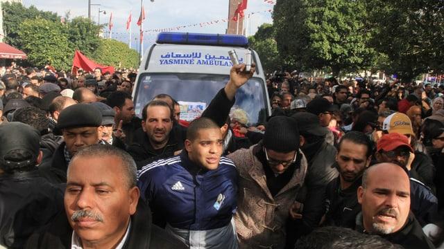 Demonstranten begleiten das den Leichnam von Chokri Belaïd transportierende Fahrzeug.