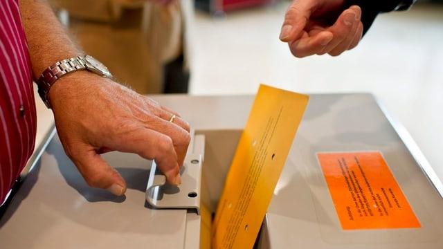 Ein Abstimmungszettel, der gerade in eine Urne fällt