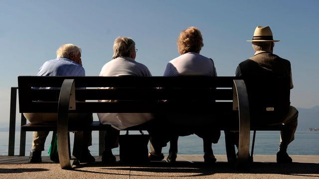 Eine Gruppe von Senioren sitzt auf einer Bank.