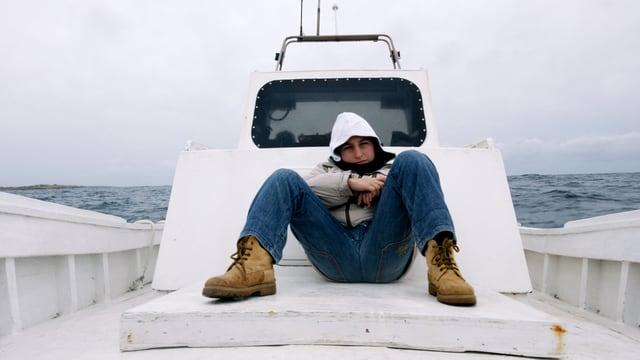 Eine Junge sitzt auf dem Deck eines Bootes, die Kapuze hochgezogen.