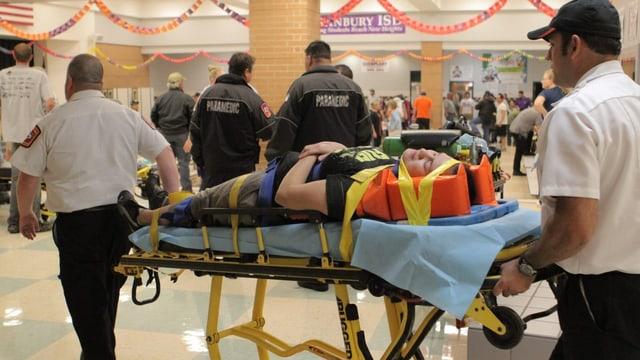 Personen tragen eine verletzte Person auf einer Bahre.
