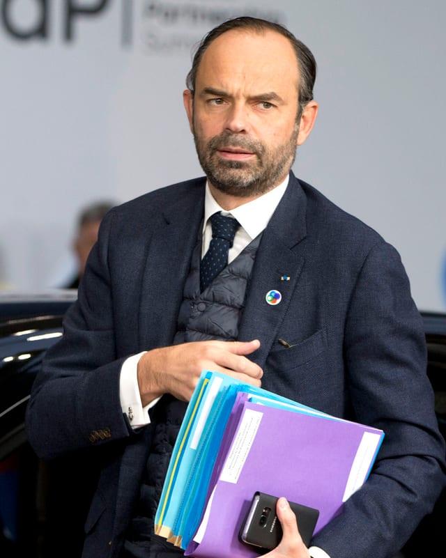 Ein Mann in Anzug und Schnellheftern unter dem Arm