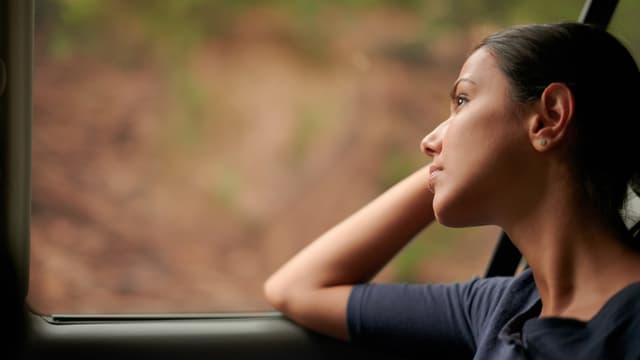 Eine Frau sitzt im Bus und schaut aus dem Fenster.