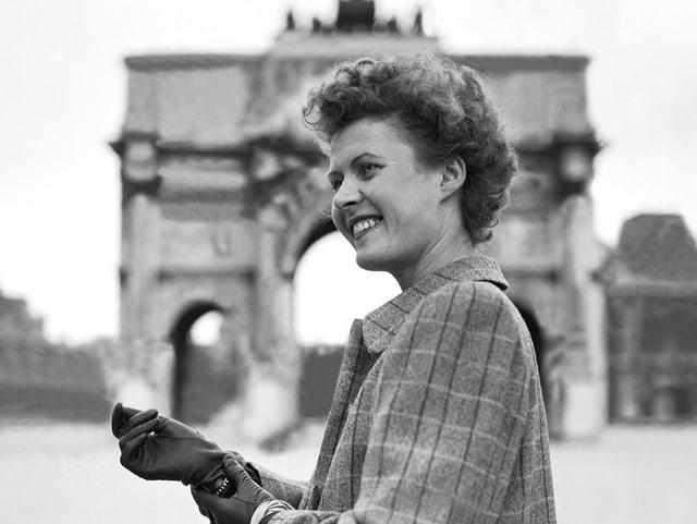 Eine junge Frau vor dem Arc de Triomphe.