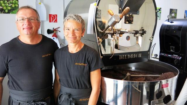 Ein Mann und eine Frau vor einer Röstmaschine.