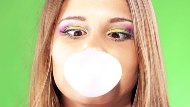 Frau bildet eine Kaugummiblase