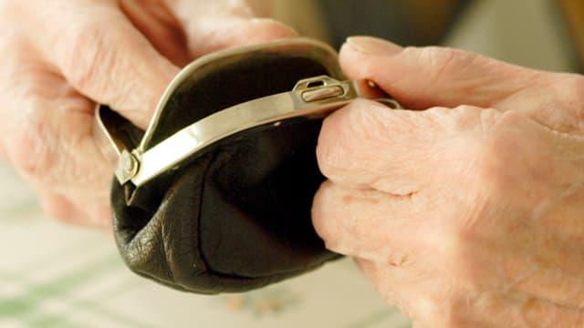 Alter Mann hält Geldbeutel in den Händen