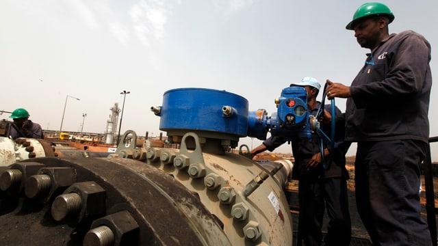 Zwei Arbeiter drehen an einem Rad an einer Ölpipeline im Sudan.