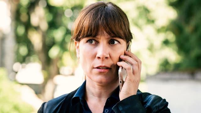 Eine Frau hält ein Telefon ans Ohr.