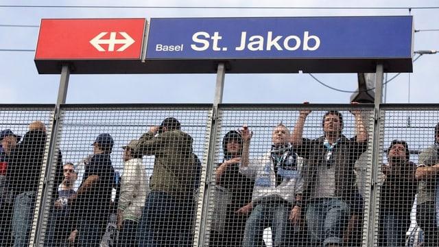 Fussballfans an der Haltestelle Basel St. Jakob hinter einer Absperrung.