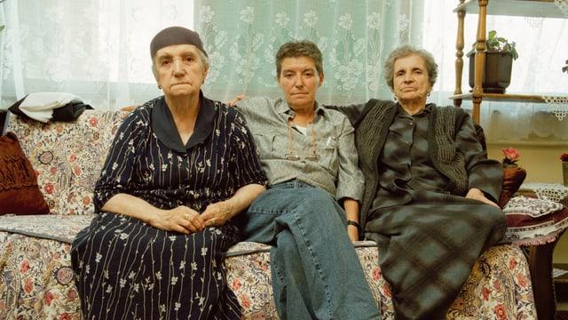 Eine Frau mit kurzen Haaren und männlicher Kleidung sitzt zwischen zwei älteren Frauen auf einem Sofa.