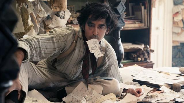 Filmszene: Ein junger Mann sitzt inmitten von beschriebenen Fetzen Papier auf dem Boden. Im Mund hat er ebenfalls einen Fetzen.