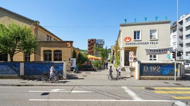 eine Strasse und ein Haus im Hintergrund mit Fussgängern
