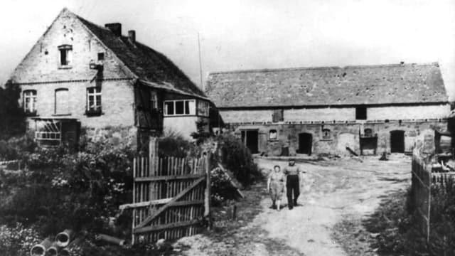 Im Hintergrund ein Bauernhof, ein Mann und eine Frau, aus dem Tor des Hofs gehend.