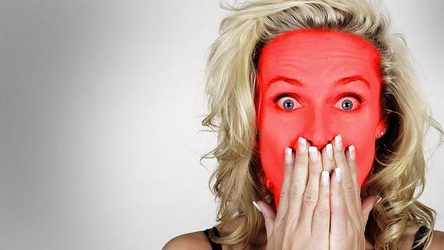 Frau mit hochrotem Kopf und weit aufgerissenen Augen hält sich die Hände vor den Mund.