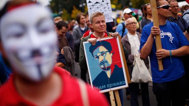 Demonstration, ein MAnn hölt ein Plakat mit einem Bild von Edward Snowden.