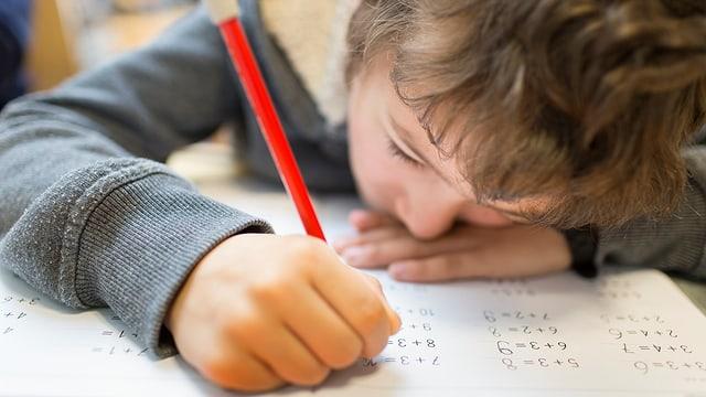 Ein Kind löst Rechenaufgaben. Im Vordergrund die Hand mit dem Bleistift
