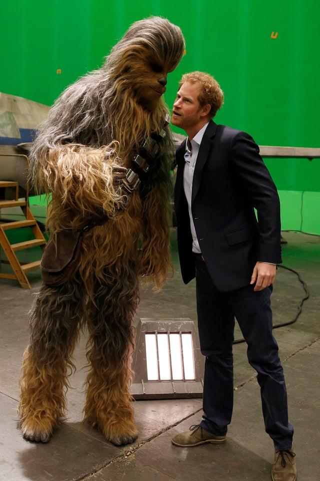 Ein Schauspieler im Chewbacca Kostüm flüsstert Prinz Harry etwas ins Ohr.