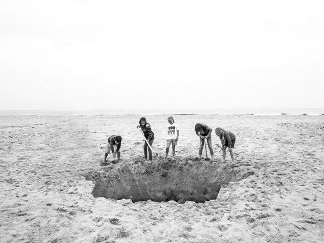 Kinder graben ein grosses Loch im Sand